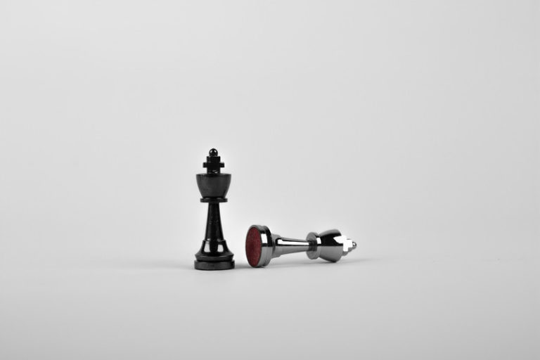 two chess pieces one standing up the other fallen over