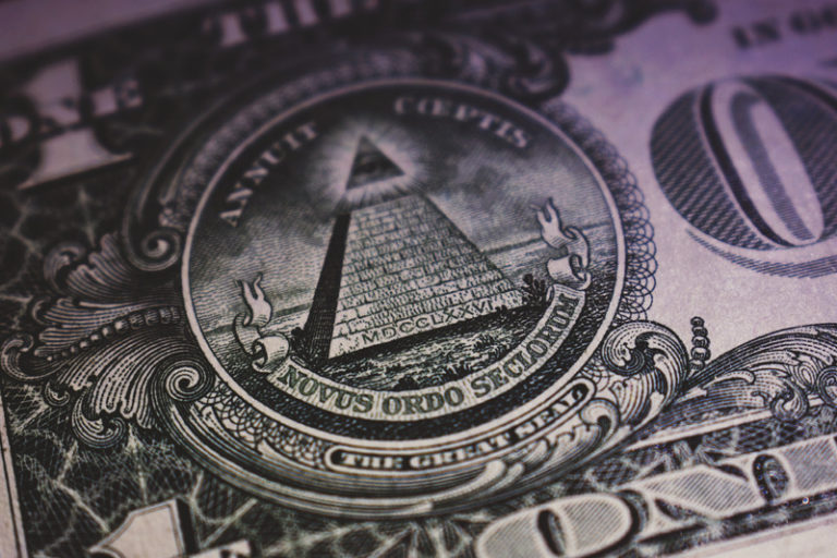 Close up of a dollar bill focusing on the all seeing eye