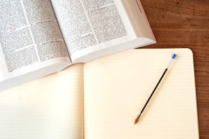 a book and notebook with a pen. It looks like its ready to take notes