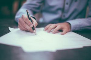 a guy signing papers on a table