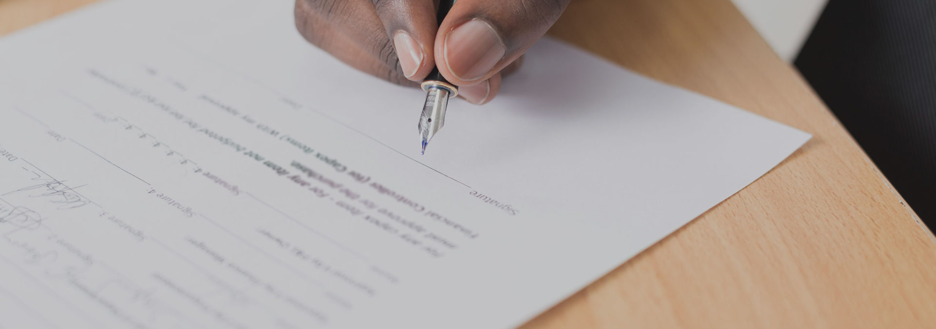 A hand holding a pen signing their name on a contract
